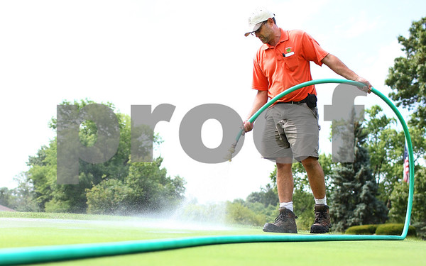 Kyle Bursaw - kbursaw@shawmedia.com<br /> <br /> Steve Tritt, the assistant superintendent at Sycamore Golf Course, waters spots on the putting green that need a little extra attention beyond what they get from the course's sprinkler system on Monday, July 23, 2012.