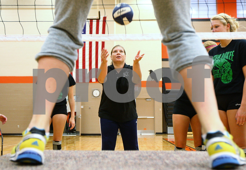 Kyle Bursaw – kbursaw@shawmedia.com<br /> <br /> Kishwaukee College volleyball coach Stephanie Gooden demonstrates a blocking drill with her assistant coach Meagan Schoenrock (on platform) during practice at DeKalb High School on Monday, Sept. 17, 2012.