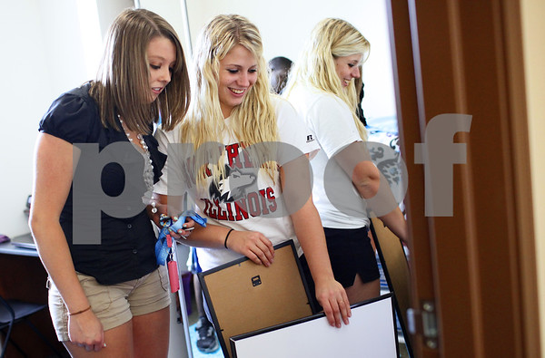 Kyle Bursaw - kbursaw@shawmedia.com<br /> <br /> Taylor Jacques (right) shows roommate Angela Versluis pictures of the two of them she plans to put up on her wall when they are allowed to in a month while unpacking their rooms in New Residence Hall on Thursday, Aug. 23, 2012.
