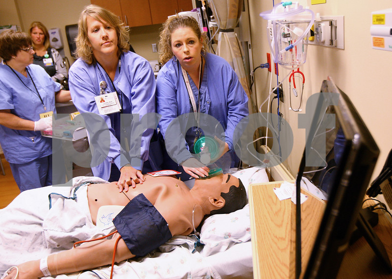 Kyle Bursaw - kbursaw@shawmedia.com<br /> <br /> Loretta Hendley (left) and Ryanne Domingue look to the monitor to view the patient's vitals while trying to save him in an emergency situation. The patient in the scenario is a new high-fidelity mannequin with the hospital