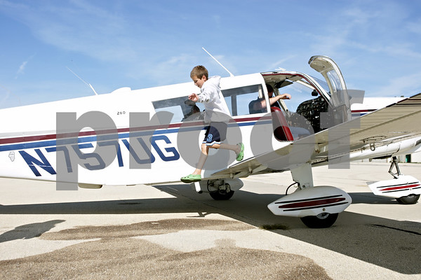 Rob Winner – rwinner@shawmedia.com<br /> <br /> Owen Brown, 8, of Genoa, hops off the wing of Steve Doonan's (right) Piper Cherokee 6 after a Young Eagles flight on Saturday, Aug. 18, 2012, at the DeKalb Taylor Municipal Airport in DeKalb, Ill.