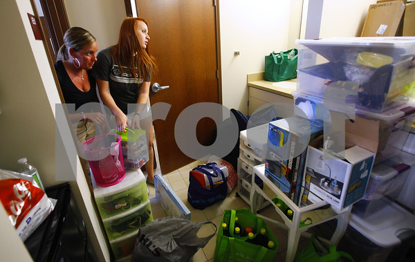 Kyle Bursaw - kbursaw@shawmedia.com<br /> <br /> Brittney Bertucci (right) and her mother Karen (left) work on unpacking a pile Brittney and roommate Karli Ferro's belongings in their shared area in New Residence Hall West on Thursday, Aug. 23, 2012.