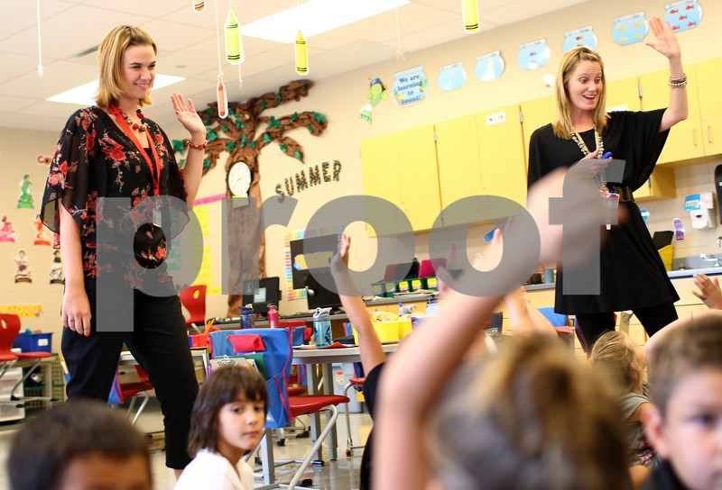 Kyle Bursaw – kbursaw@shawmedia.com<br /> <br /> North Grove Elementary teacher Kim Payne (right) and NIU student and 'teacher candidate' Kara Christensen raise their hands when polling the class<br /> on Wednesday, Aug. 29, 2012. North Grove and NIU have partnered to increase the length and responsibilities of their student teaching program, placing aspiring teachers, like Christensen, in a classroom for a full academic year.