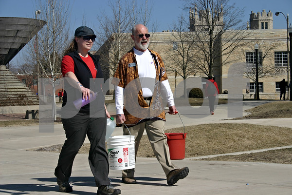 Stephanie Hickman - shickman@shawmedia.com<br /> <br /> Jenny Krug (left) walks with Dr. Kurt Thurmaier (right) as they carry water around the Martin Luther King Jr. Commons on the NIU campus Thursday for the Walk with Water fundraiser.