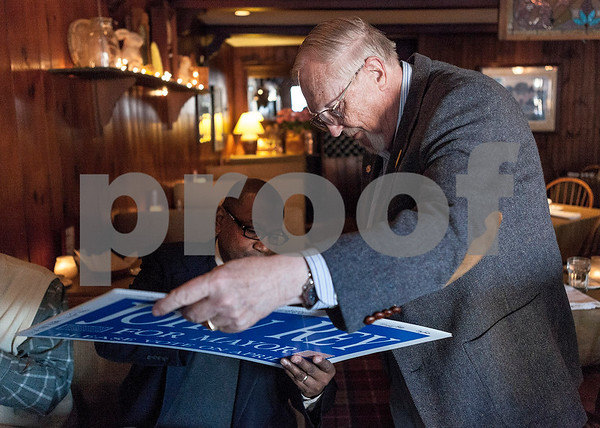 "Erik Anderson - For the Daily Chronicle <br /> Ellingsworth Webb (left), campaign manager for John Rey, signs a ""John Rey for Mayor"" sign as Barry Schrader holds it at the Hillside Restaurant in downtown DeKalb on Thursday, March 28, 2013. The attendees at the fundraiser autographed the sign for Arlene Neher, a co-host for the fundraiser who had triple bypass surgery and could not attend the event."