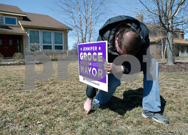 "Erik Anderson - For the Daily Chronicle<br /> Eric Groce, Jennifer's husband puts a, ""Jennifer Groce for Mayor"" sign into the ground in the yard of homeowner David Castle while campaigning in the Fairway Oaks subdivision in DeKalb on Saturday, March 23, 2013."