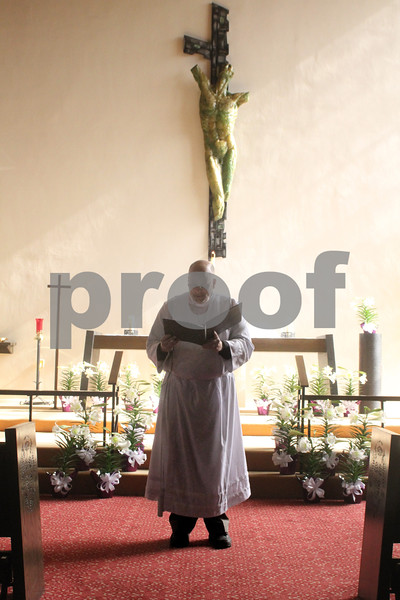 With the altar area bathed in sunlight, Pastor Dan Wynard of the Bethlehem Evangelical Lutheran Church in DeKalb reads a prayer during Easter Worship on Sunday.