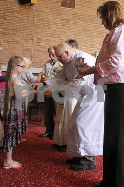 Pastor Dan Wynard offers Communion to 10 year old Abbey Brooks during Easter Services at the Bethlehem Evangelical Lutheran Church on Sunday.
