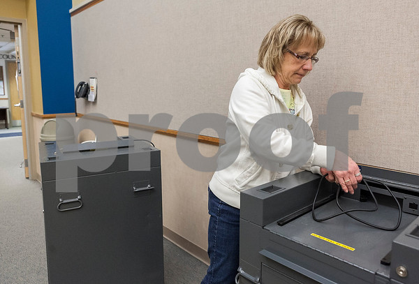 Erik Anderson - For the Daily Chronicle <br /> Chief Deputy of Election MaryLynne Meich wraps up the power cable of a voting machine before transferring it to the DeKalb County Legislative Building from the Administration Building in Sycamore on Saturday, April 6, 2013.