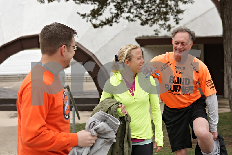 Rob Winner – rwinner@shawmedia.com<br /> <br /> David Kuhn (right), of DeKalb who is legally blind, leans on the shoulder of guide Sarah Garman (center), of Sycamore, while removing his track pants as Bryon Guida, of Oregon, watches before a run at Hopkins Park in DeKalb, Ill., Friday, April 12, 2013. Kuhn and Guida will be traveling to Massachusetts this weekend to participate in the 2013 Boston Marathon this Monday.