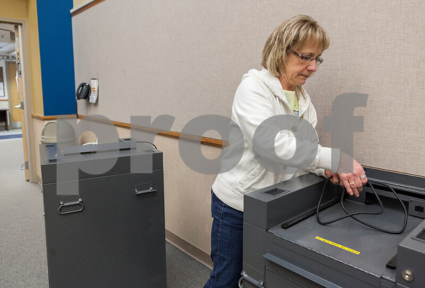 Erik Anderson for Shaw Media<br /> <br /> Chief Deputy of Election MaryLynne Meich wraps up the power cable of a voting machine before transferring it to the DeKalb County Legislative Building from the Administration Building in Sycamore on Saturday, April 6, 2013.