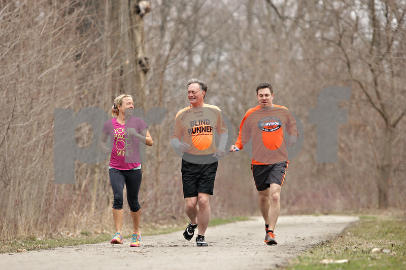 Rob Winner – rwinner@shawmedia.com<br /> <br /> David Kuhn (center), of DeKalb who is legally blind, runs with guides Sarah Garman (left), of Sycamore, and Bryon Guida, of Oregon, at Hopkins Park in DeKalb, Ill., Friday, April 12, 2013. Kuhn and Guida will be traveling to Massachusetts this weekend to participate in the 2013 Boston Marathon this Monday.