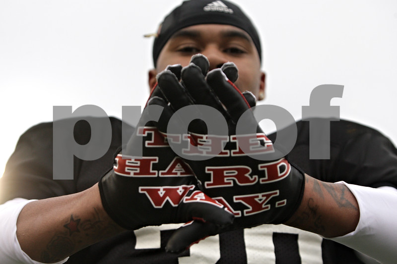 "Rob Winner – rwinner@shawmedia.com<br /> <br /> Northern Illinois cornerback Marlon Moore holds up his hands which shows the words ""The Hard Way,"" on his gloves during practice at Huskie Stadium in DeKalb, Ill., Friday, April 12, 2013."