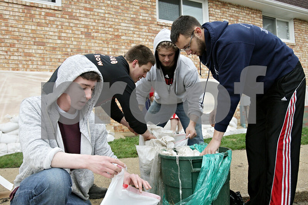 Rob Winner – rwinner@shawmedia.com<br /> <br /> Northern Illinois students Gabe Smith (from left to right), Rory Dudas, Brett Placek, and Jake Suckow clean up at Ashbury Court Apartments after sand bagging the garden apartment windows in DeKalb, Ill., Thursday, April 18, 2013. Smith is from Sigma Alpha Mu and Dudas, Placek and Suckow are from Phi Sigma Kappa.