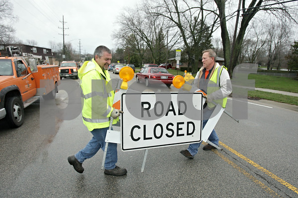 Rob Winner – rwinner@shawmedia.com<br /> <br /> City of DeKalb employees Johnn Lucius (left) and Ted Jouris close down Taylor Street near Lions Park due to flooding of the Kishwaukee River in DeKalb, Ill., Thursday, April 18, 2013.