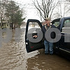 Rob Winner – rwinner@shawmedia.com<br /> <br /> Evergreen Village Mobile Home Park resident Larry Hunter waits on a flooded street for a family member to retrieve some items from her home in Sycamore, Ill., on Thursday, April 18, 2013.