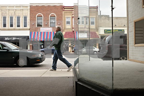 Rob Winner – rwinner@shawmedia.com<br /> <br /> Ralph Busch, of Sandwich, walks past an empty store front on the 200 block of East Lincoln Highway on his way to The Lincoln Inn Restaurant in downtown DeKalb, Ill., Friday, April 12, 2013.
