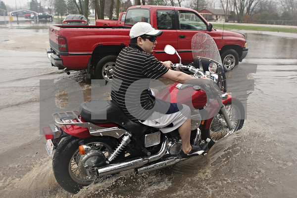 Rob Winner – rwinner@shawmedia.com<br /> <br /> Evergreen Village Mobile Home Park resident Alejandro Lara drives off on his motorcycle down a flooded street in Sycamore, Ill., on Thursday, April 18, 2013.