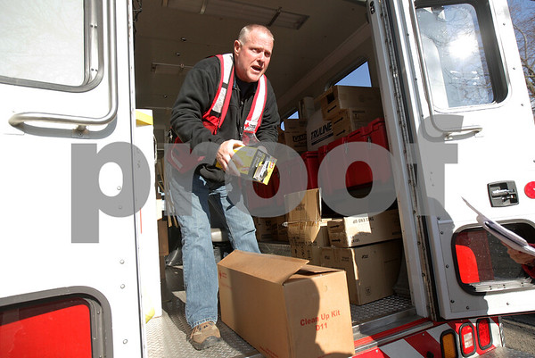 Monica Maschak - mmaschak@shawmedia.com<br /> Red Cross volunteer Dean Richardson prepares cleaning supplies and disaster kits to distribute to those living in Evergreen Village in Sycamore for the second day in a row on Wednesday, April 24, 2013. The DeKalb County Red Cross Disaster Action Team estimated some 300 items were handed out to the residents of the approximately-160-trailer community that was recently flooded due to heavy rains last week. Among the items were trash bags, shovels, rakes, tarps and gloves. The Red Cross plans to visit the community again on Thursday to distribute water.