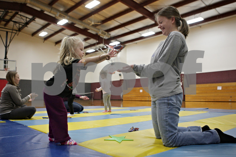 Rob Winner – rwinner@shawmedia.com<br /> <br /> Katie Miller (left), 2 of DeKalb, tosses a bean bag to her mother, Lisa Miller, during a Tumble Tots class at the Haish Gymnasium in DeKalb, Ill., Monday, April 15, 2013.