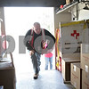 Monica Maschak - mmaschak@shawmedia.com<br /> Red Cross volunteer Dean Richardson retrieves cleaning supplies and disaster kits from the truck to distribute to those living in Evergreen Village in Sycamore for the second day in a row on Wednesday, April 24, 2013. The DeKalb County Red Cross Disaster Action Team estimated some 300 items were handed out to the residents of the approximately-160-trailer community that was recently flooded due to heavy rains last week. Among the items were trash bags, shovels, rakes, tarps and gloves. The Red Cross plans to visit the community again on Thursday to distribute water.