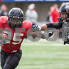 Erik Anderson - For the Daily Chronicle <br /> Northern Illinois University running back Giorgio Bowers fends off an opposing player during the NIU Huskie Bowl at Huskie Stadium on Brigham Field on Saturday, April 20, 2013. The cardinal team defeated the black team.