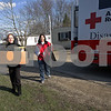 Monica Maschak - mmaschak@shawmedia.com<br /> Monica San Pedro carries a disaster kit as Red Cross volunteer Tracy Lesiak helps carry a rake back to San Pedro's car during a trip to distribute cleaning supplies and disaster kits to the residents of Evergreen Village in Sycamore on Wednesday, April 24, 2013. The DeKalb County Red Cross Disaster Action Team estimated some 300 items were handed out to the residents of the approximately-160-trailer community that was recently flooded due to heavy rains last week. Among the items were trash bags, shovels, rakes, tarps and gloves. The Red Cross plans to visit the community again on Thursday to distribute water.