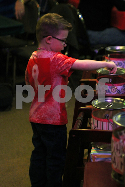 """Gavin Slack, nephew to """"old fat guys"""" member Larry Meredith, puts money in the donation bin for the Susan G. Komen 3-Day during Saturday's cancer benefit in Waterman on Saturday."""