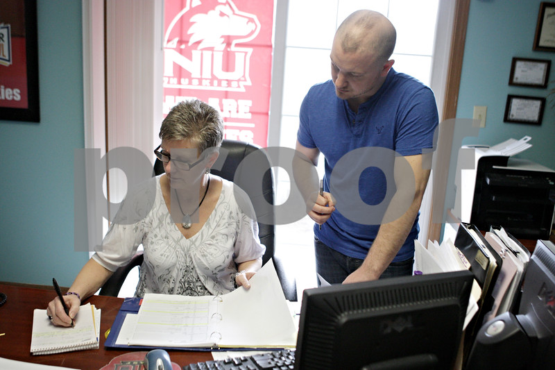 Rob Winner – rwinner@shawmedia.com<br /> <br /> Secretary Nanette Murray (left) and her son, J.T. Murray the office manager at Pittsley Realty in DeKalb, Ill., check the availability of apartments in July for a client in their offices on Thursday, April 25, 2013. Beginning in 2015, incoming freshmen will have to live in the dormitories for their first two years of college.