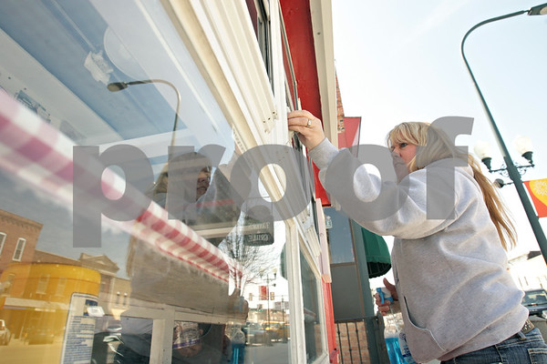 Rob Winner – rwinner@shawmedia.com<br /> <br /> Cassie Oltman cleans the windows of Cassie's Popcorn Stand in downtown Sycamore, Ill., Monday, April 22, 2013. The popcorn stand will be opening this Sunday.