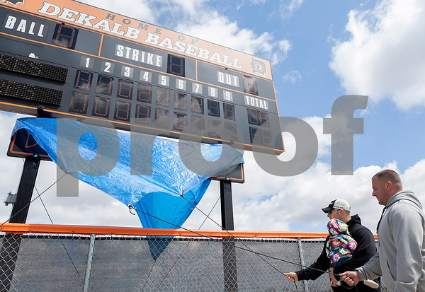 """Erik Anderson - For the Daily Chronicle <br /> Sons, Kyle Pettengell, his daughter Ava (left) and Ryan Pettengell (right) pull drawstrings releasing the blue tarp to present the new """"Dave Pettengell Field"""" sign at DeKalb High School on Saturday, April 20, 2013."""