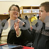 Rob Winner – rwinner@shawmedia.com<br /> <br /> Christy Niemeyer (left), a direct support person, and Danny Hedberg, who is autistic, react after Hedberg successfully finishes a learning program while using a computer tablet at Opportunity House in Sycamore, Ill., Friday, April 19, 2013. The Opportunity House day program in Sycamore helps prepare individuals with disabilities to live more independent by teaching life skills.
