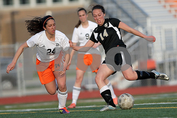 Monica Maschak - mmaschak@shawmedia.com<br /> DeKalb's Rachel Torres competes for the ball as Sycamore's Katherine Kohler winds up for a kick during the first half of a match on Tuesday, April 30, 2013.