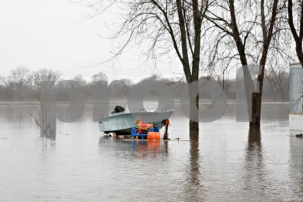 Rob Winner – rwinner@shawmedia.com<br /> <br /> A boat and some items are seen near the edge of the Kishwaukee River within the Evergreen Village Mobile Home Park in Sycamore, Ill., on Thursday, April 18, 2013.