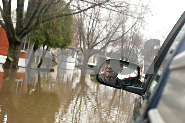 Rob Winner – rwinner@shawmedia.com<br /> <br /> Evergreen Village Mobile Home Park resident Larry Hunter drives his pickup truck down a flooded street at the park while looking for fellow residents that may need help in Sycamore, Ill., on Thursday, April 18, 2013.