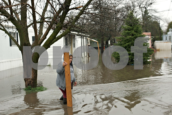 Rob Winner – rwinner@shawmedia.com<br /> <br /> A woman is seen holding a board to help keep her footing while walking on a flooded street at Evergreen Village Mobile Home Park in Sycamore, Ill., on Thursday, April 18, 2013.
