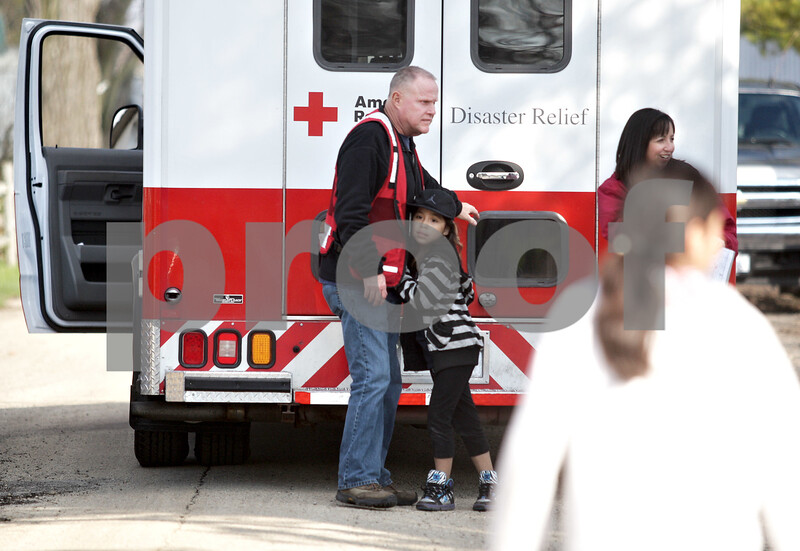 Monica Maschak - mmaschak@shawmedia.com<br /> Red Cross volunteer Dean Richardson receives a hug from resident Yesse Vega, 9, during a trip to hand out cleaning supplies and disaster kits to those living in Evergreen Village in Sycamore for the second day in a row on Wednesday, April 24, 2013. The DeKalb County Red Cross Disaster Action Team estimated some 300 items were handed out to the residents of the approximately-160-trailer community that was recently flooded due to heavy rains last week. Among the items were trash bags, shovels, rakes, tarps and gloves. The Red Cross plans to visit the community again on Thursday to distribute water.
