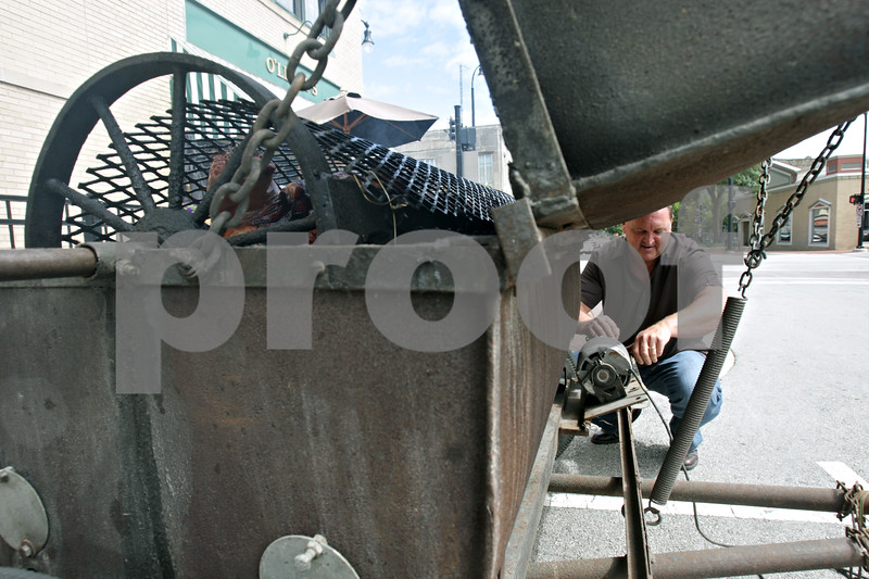 Rob Winner – rwinner@shawmedia.com<br /> <br /> Mel Witmer, owner of O'Leary's Restaurant and Pub, performs maintenance on a roaster as a 200-pound pig cooks outside the business during BaconPalooza in downtown DeKalb, Ill., Saturday, July 27, 2013, as part of Kishwaukee Fest.