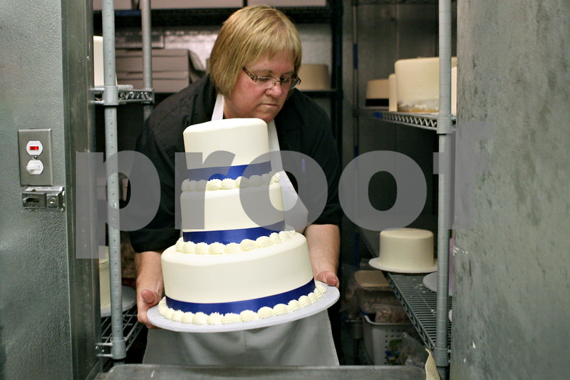 Rob Winner – rwinner@shawmedia.com<br /> <br /> Deanna Watkins owner of Sweet Dream Desserts and Catering carefully places a finished three-tier wedding cake into the freezer after decorating it at her business in Sycamore, Ill., Thursday, Aug. 1, 2013.