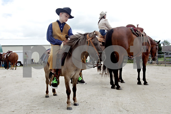 Rob Winner – rwinner@shawmedia.com<br /> <br /> Joshua Hayes, 11, of Rockford looks down at his miniature horse at Amber Sun Acres in Malta, Ill. before the start of the Northern Illinois Outlaws' cowboy mounted shooting event on Saturday, July 27, 2013, as part of Kishwaukee Fest.