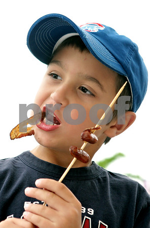 Rob Winner – rwinner@shawmedia.com<br /> <br /> DeKalb resident Dekker Surratt, 7, enjoys a bacon wrapped frank skewer during BaconPalooza at the Frank Van Buer Plaza in downtown DeKalb, Ill., Saturday, July 27, 2013, as part of Kishwaukee Fest.