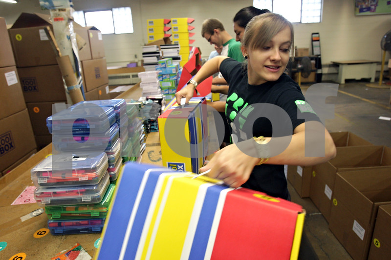Rob Winner – rwinner@shawmedia.com<br /> <br /> Racquel Rossbach lifts two boxes filled with school supplies to be placed into a larger box that will be shipped to a New Jersey school at School Tool Box in Sycamore, Ill., Tuesday, July 30, 2013.