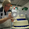 Rob Winner – rwinner@shawmedia.com<br /> <br /> Deanna Watkins owner of Sweet Dream Desserts and Catering decorates a three-tier wedding cake at her business in Sycamore, Ill., Thursday, Aug. 1, 2013.