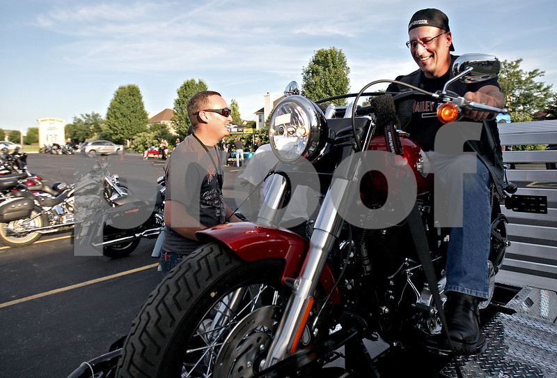 """Monica Maschak - mmaschak@shawmedia.com<br /> DeKalb Harley Davidson Parts Associate Justin Wiltse watches as Brian Rosenquist, of Sycamore, tests out the new Harley Davidson Softail Slim hooked up to a """"Jumpstart"""" at a bike night held by Midwest Women Riders at Cabana Charley's on Thursday, August 1, 2013. All proceeds from the night went to Safe Passage, a domestic violence shelter. Midwest Women Riders inspires, promotes and encourages female motorcycle riders and also emphasizes the importance of other motorists seeing motorcycles."""
