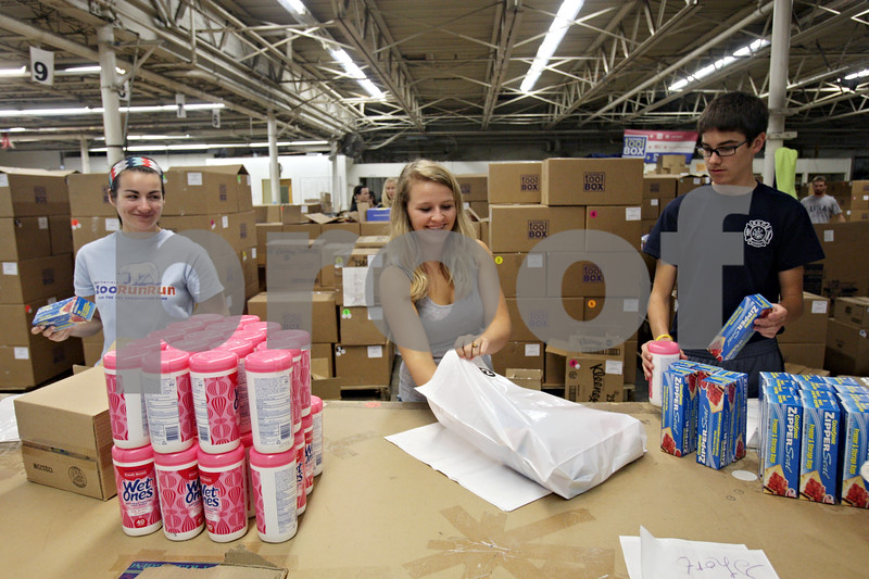 Rob Winner – rwinner@shawmedia.com<br /> <br /> (From left to right) Denise Dolder, Betsy Koehnke, and Connor Hickey pack school supplies to be shipped to a Sycamore school at School Tool Box in Sycamore, Ill., Tuesday, July 30, 2013.