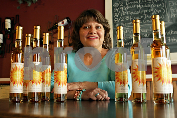 Rob Winner – rwinner@shawmedia.com<br /> <br /> Marla Shega is seen surrounded by bottles of wine with her illustration on the bottles at Prairie State Winery in Genoa, Ill., Tuesday, Aug. 6, 2013.