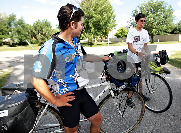 Monica Maschak - mmaschak@shawmedia.com<br /> Brandon Morris, 24, and Garrett Morris, 21, from the Los Angeles area make a pit stop in DeKalb on Saturday, August 3, 2013. The Morris brothers are biking from Oregon to New York in efforts to raise funds for a San Luis Obispo non-profit called Project Hope and Fairness. Project Hope and Fairness is focused on ending the injustices of the cocoa trade by empowering cocoa farmers in Africa and shortening the distance between those who eat chocolate and those who grow the beans.