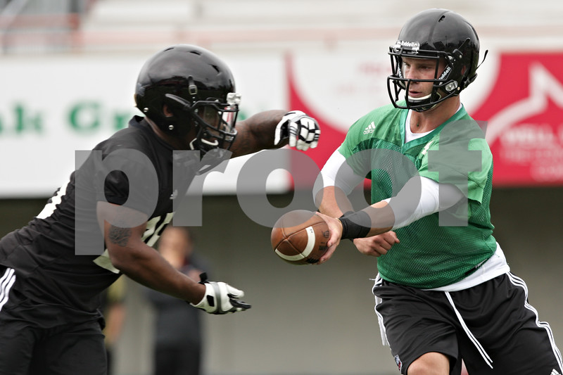 Rob Winner – rwinner@shawmedia.com<br /> <br /> Quarterback Jordan Lynch (right) hands off the ball to running back Giorgio Bowers during the first practice of the season at Northern Illinois University in DeKalb, Ill., Monday, Aug. 5, 2013.