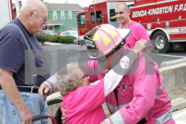 Rob Winner – rwinner@shawmedia.com<br /> <br /> Genoa resident Bob Probst (left) watches as his wife Bevia Probst, a breast cancer survivor, is hugged by Eddie McDonald, a firefighter from Orange Beach, Ala., during the Pink Heals Tour outside Pete's Castle in Genoa, Ill., Monday, Aug. 5, 2013. The Pink Heals Tour has traveled the country to raise cancer awareness and to honor and support those who have fought and are battling all types of cancer.