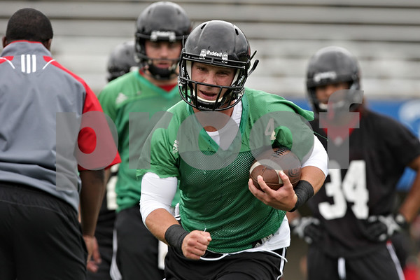 Rob Winner – rwinner@shawmedia.com<br /> <br /> Quarterback Jordan Lynch carries the football during a drill at the first practice of the season at Northern Illinois University in DeKalb, Ill., Monday, Aug. 5, 2013.